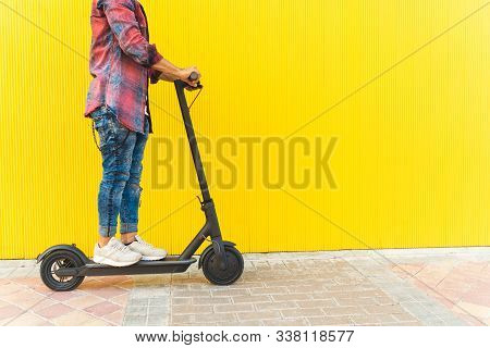 Man On An Electric Scooter Over Yellow Background. Close Up Of A Young Man On Electric Scooter Outdo