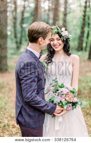 Bride And Groom In Forest Kissing. Newlyweds Bride And Groom At A Wedding In Nature, Green Forest, A