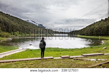 A Tourist Girl Standing Next To Lake Engolasters, In The Encamp Parish Of Andorra, Is A Lake Formed