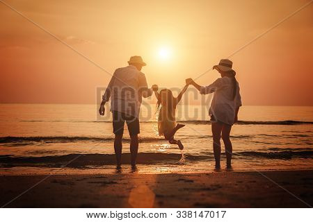 Summer Vacation, Happy Family Jumping Together On The Beach In Holiday.
