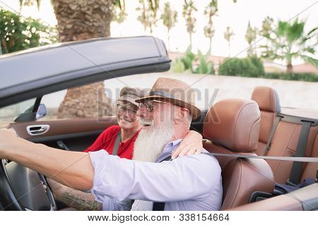 Couple Inside A Convertible Car In A Romantic Moment  - Retired Couple Having Fun Doing A Road Trip