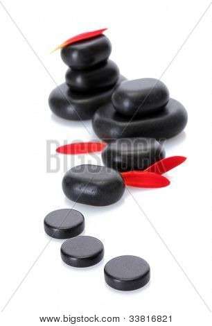 Spa stones and red petals isolated on white