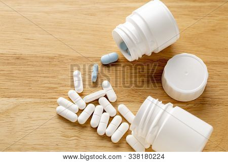 The White And Blue Pills Are By The Medicine Bottle