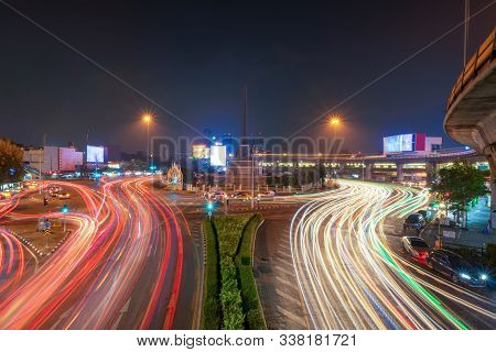 Victory Monument With Car Light Trails On Street Road In Bangkok Downtown Skyline. Thailand. Financi