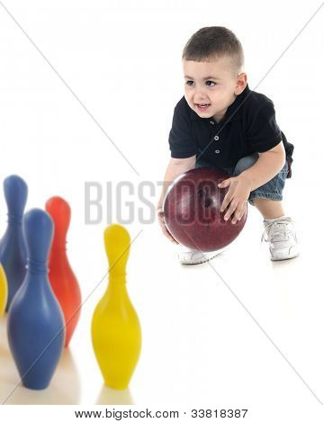 An adorable preschooler attempting to bowl a heavy bowling ball to knock down his toy plastic pins.  Focus on child.  On a white background.