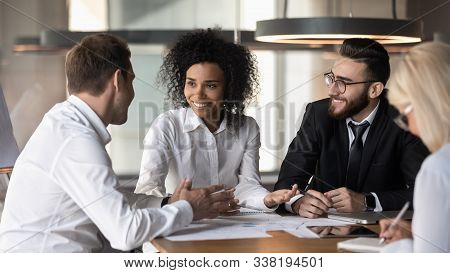 Smiling Diverse Colleagues Discuss Business Ideas At Team Briefing