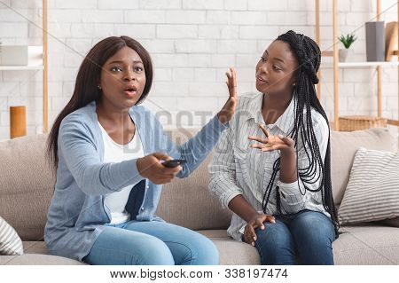 Indifference In Friendship. Young Black Woman Watching Television Not Paying Attention To Her Friend