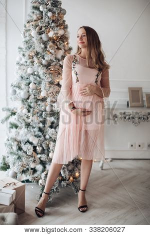 Close-up Tenderness Female Hand Hugging Pregnant Tummy Feeling Fondness At Christmas Tree