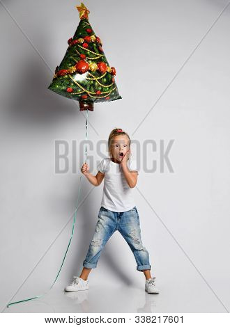 Little Kid Girl In Full Growth With Christmas Tree Air Balloon Is Awing, Surprised, Worrying, Scared