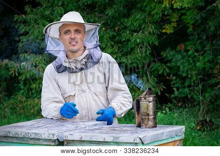 Young Beekeeper Working In The Apiary. Professional Beekeeper Working Outdoors And Wearing The Prote