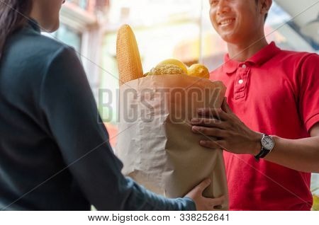 Food Delivery Service Man In Red Uniform Smiling Handing Fresh Food To Recipient And Young Woman Cus
