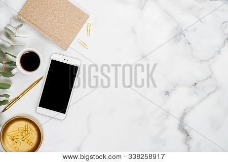 White Marble Office Desk Table With Smartphone Screen Mockup, Gold Paper Notebook, Eucalyptus Leaf,