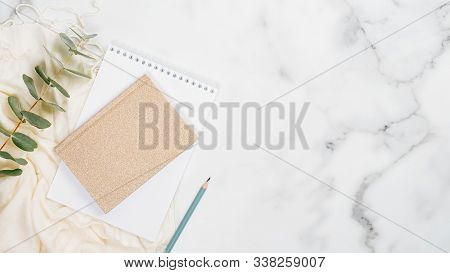 Home Office Desk Table Concept. Minimal Flat Lay Style Composition With Paper Notebook, Pencil, Euca
