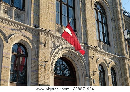 Riga / Latvia - 01 December 2019: Entrance To The Building University Of Latvia. Latvia Flag Waving