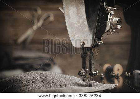 Old Antique Sewing Machine With Linen Cloth. In The Background Is A Hanging Tailoring Scissors. Retr