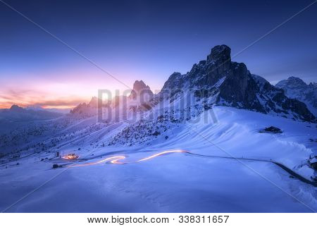 Snowy Mountains And Blurred Car Headlights On The Winding Road At Night In Winter. Beautiful Landsca