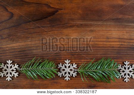 Christmas Or New Year Decoration Background. Fir And Snowflakes  On Wooden Background With Copy Spac