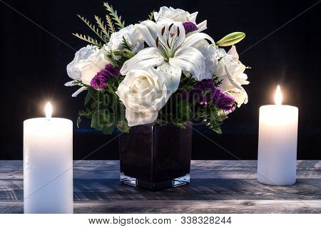 Bouquet Of White Flowers In A Purple Vase, White Candle On A Wooden Boards. Vintage Home Decor Dark