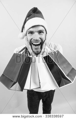 Happy Holidays Celebration. Man In Santa Hat With Bags On Orange Background. Christmas, New Year Sur