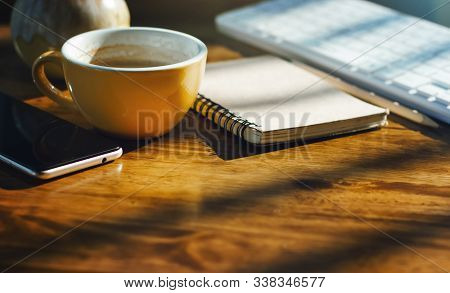 Place Of Work On Wooden Desk With Cup Of Coffee, Notebook, Mobile Phone And Computer Keyboard. Backg