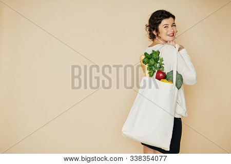 Cheerful Young Woman Using Linen Reusable Bag When Shopping For Groceries