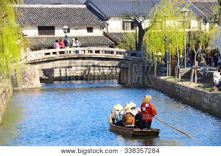 Tourists in old-fashioned boat, Kurashiki canal inn Bikan district, Kurashiki city, Japan