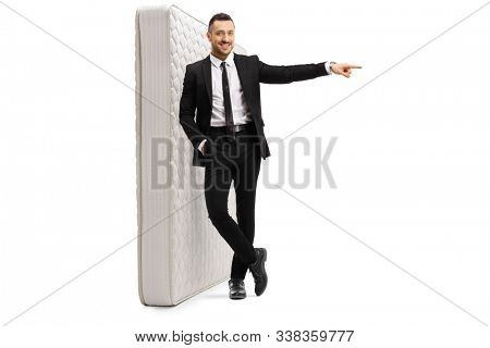 Full length portrait of a young cheerful man in a black suit standing and leaning on a mattress and pointing to the side isolated on white background