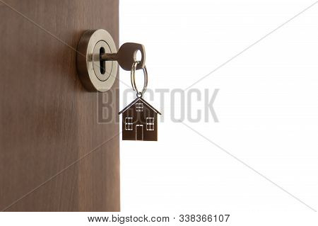 Open Door To A New Home. Key And Home Shaped Keychain, Isolated. Mortgage, Investment, Real Estate,