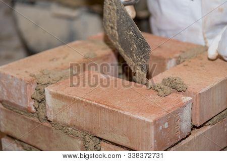 Craftsman Builds Bricks Wall With Small Bricks - Closeup Bricklayer