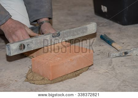 Mason Builds Brick Wall And Measures With Spirit Level - Close-up