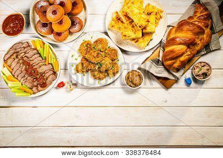 Selection Of Traditional Hanukkah Food For Festive Dinner - Potato Latkes, Applesauce, Challah, Beef