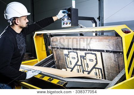 Worker In A Hard Hat Turning On A Punching Machine. Cardboard Boxes Factory. Paper Die Cutting Machi