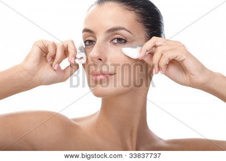 Attractive young woman wiping away eye makeup by cotton pad.