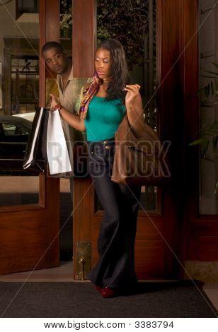 Mulher negra com sacolas homem olhando para ela