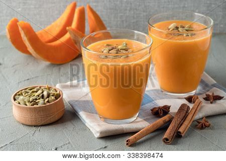 Glasses With Tasty Pumpkin Smoothie On Grey Table. Homemade Gourd Mousse. Delicious Autumn Blended D