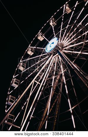 Ferris Wheel. A Ferris Wheel Rotates Against The Background Of The Night Sky. Close-up Of A Ferris W