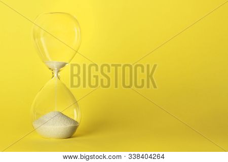 Time Is Running Out Concept. An Hourglass On A Vibrant Yellow Background With A Place For Text