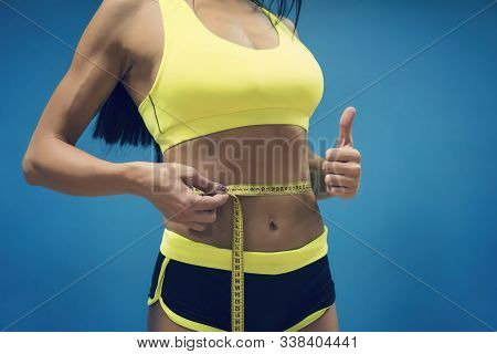 Crop Shot Of Fitness Woman In Sport Outfit Measuring Waistline With Metric Tape And Showing Thumb Up