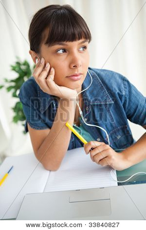 Female student demotivated to do her homework while listening music