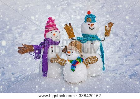 Funny Snowman Family In Stylish Hat And Scarf On Snowy Field. Happy Winter Time. Happy Funny Snowman