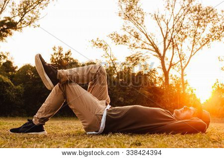 Young Man Lying Down On The Green Grass, Enjoying A Sunset Relaxation In A Park. Concept Of Freedom
