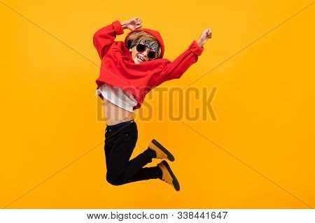 Handsome Boy With A Bandana On His Head In A Red Hoodie With Glasses Jumps On An Isolated Orange Bac