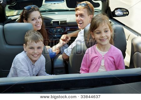 Young couple sits in cabriolet on front seats looking back, two children sit backwards on backseats, everybody laugh, back view
