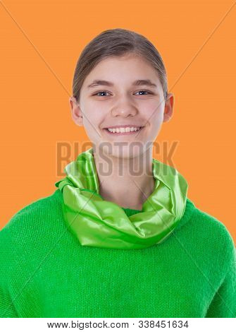 Portrait Of A Smiling Girl In A Green Sweater And A Green Neckerchief