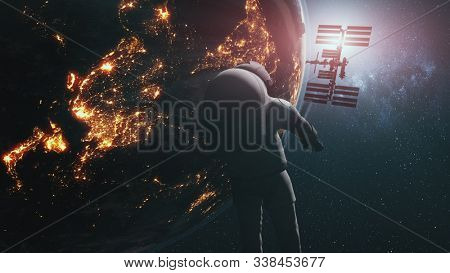 Realistic astronaut ISS revolving above Earth. Planet orbit illuminated continent. International Space Station starlight galaxy background. 3d animation. Elements of this media furnished by NASA.