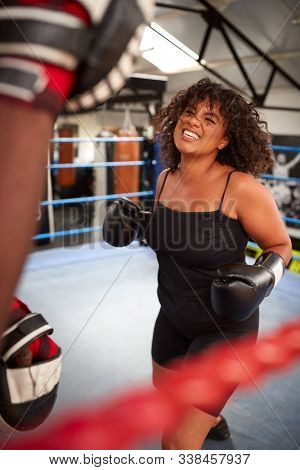 Male Personal Trainer Sparring With Female Boxer In Gym Using Training Gloves