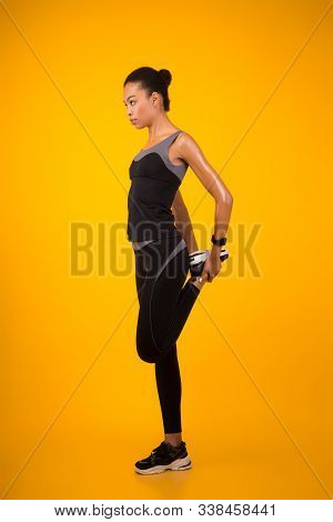Sporty Black Woman Stretching Leg Warming Up Before Workout Standing Over Yellow Studio Background.