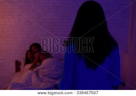 Cheating And Infidelity. Girlfriend Catching Unfaithful Boyfriend With Another Woman Lying In Bed At