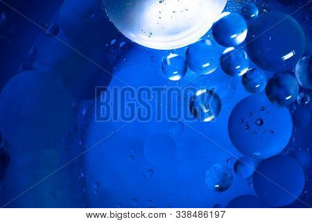 A bottle in water with air bubbles. Blue abstract background. Illuminated liquid surface. Macro photo.