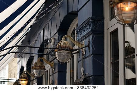 Vintage Metal Lanterns At A Facade Of Historic Building With Blue And White Striped Textile Awning